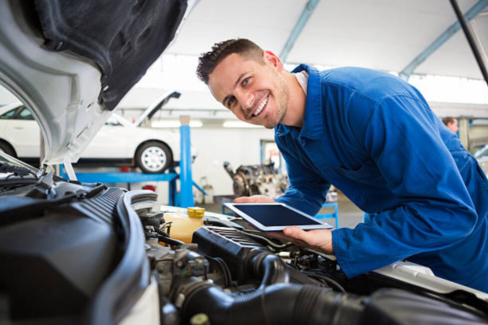 Mechanic using tablet on car at the repair garage